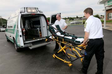 EMTs placing a gurney in an ambulance